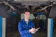 Mechanic preparing checklist under car