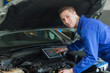 Confident mechanic using digital tablet