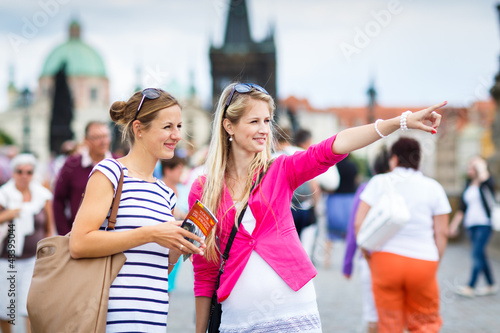 Foto  Two female tourists walking along the Charles Bridge