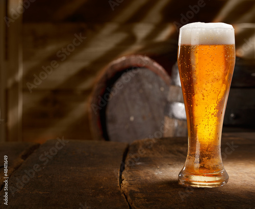 Glass of foamy beer on a table in a beer cellar