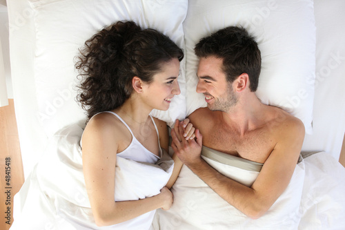 Couple lying in bed Canvas Print
