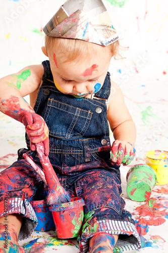Photo  süßes kleines Kind in Latzhosen mit Pinseln und Farben