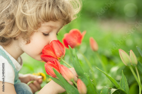 Fotografie, Obraz  Child smelling tulip