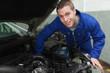 Happy mechanic repairing under car hood