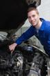 Young mechanic repairing car engine
