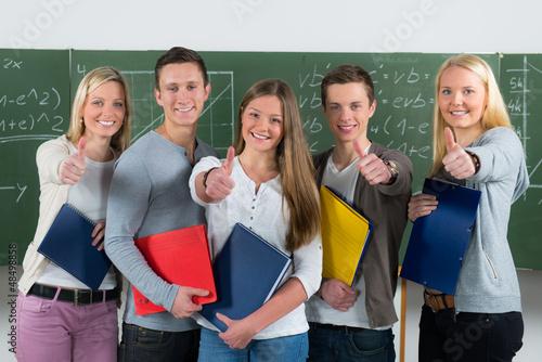 Photo motivierte schülergruppe zeigt daumen hoch