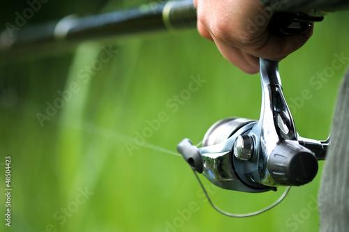 Fényképezés  Fisherman holding rod (reel) Catch trench, crucian, bremes etc