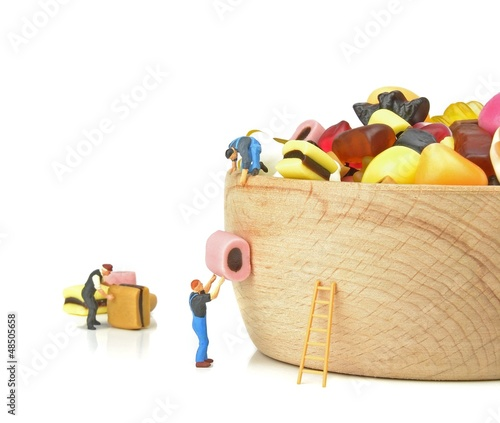 Fotografie, Obraz  Miniature workmen filling a bowl with sweets in teamwork concept