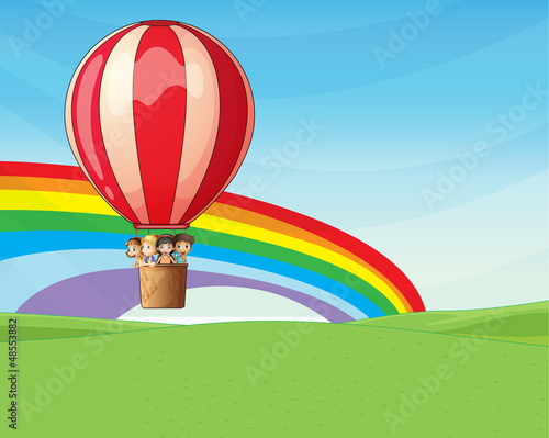 In de dag Regenboog Children riding on a hot air balloon