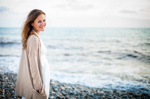Valokuva  Young woman on the beach enjoying a warm summer evening