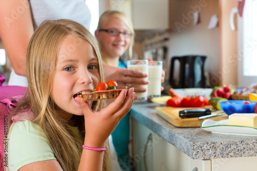 Fototapeta Family - mother making breakfast for school obraz