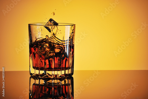 Photo Glass of whisky with ice against yellow background