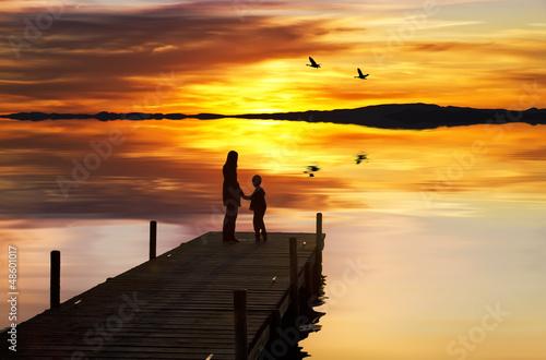 In de dag Pier madre e hijo disfrutando de la puesta de sol