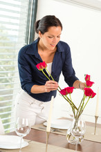 Young Woman Arranging Flowers Dinner Table