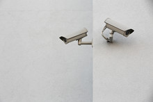 Two Security Cameras On A Wall.