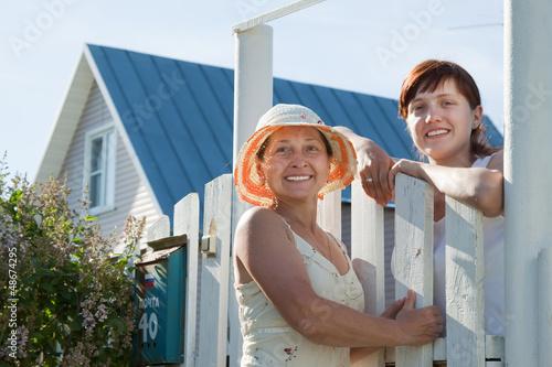 Fotografía  Two happy women near fence wicket