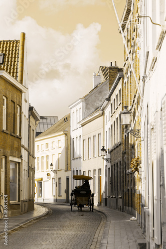 Tourists in a phaeton go on ancient streets of Bruges, Belgium