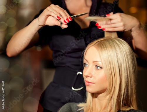 Fotografie, Obraz  Hairdresser cutting client's hair in beauty salon.