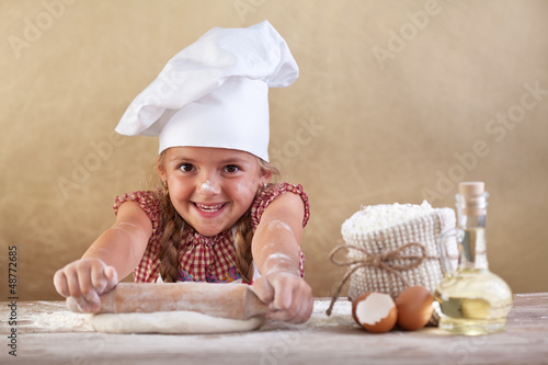 Fotografía  Happy little chef stretching the dough