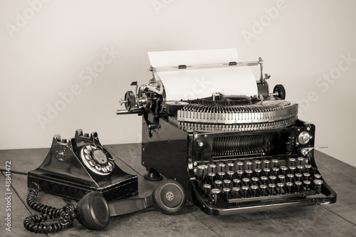 Obraz w ramie Vintage phone, old typewriter on table desaturated photo