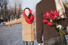 Chinese Boyfriend Holding Flowers For Ice Skating Girlfriend
