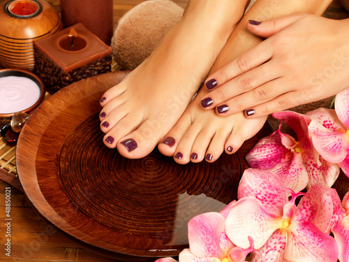 Poster Pedicure female feet at spa salon on pedicure procedure
