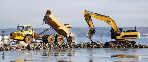 Valokuva  bulldozer dredging with truck delivering rocks