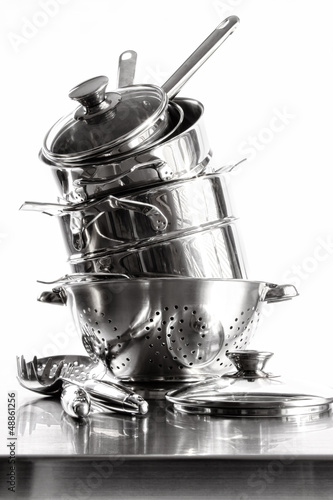 Fotografía  Stack with stainless steel pots and pans on white