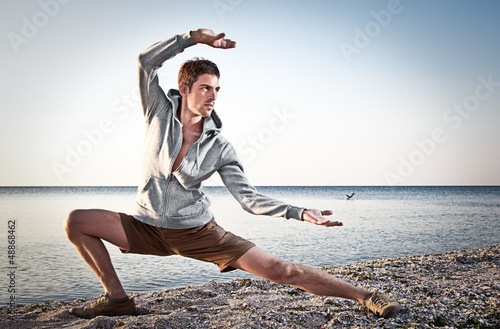 фотографія  Young attractive man making Thai-chi movements
