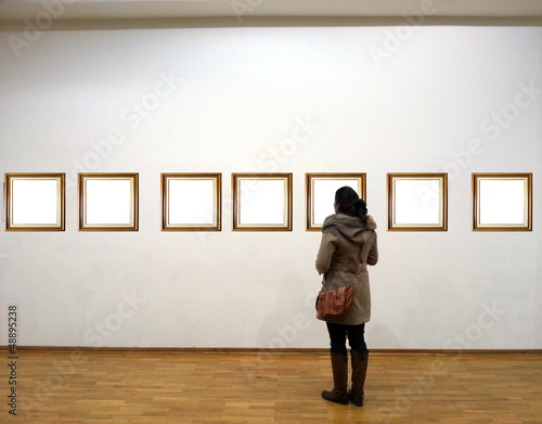 Fotografie, Obraz  Woman in gallery room looking at empty frames