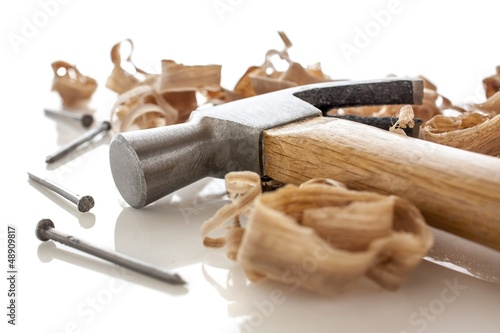 Fotografie, Obraz  hammer and nails on a wood board with sawdust shavings