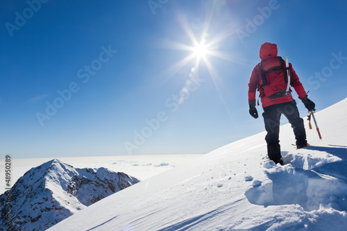 Mountaineer reaches the top of a snowy mountain in a sunny winte Canvas Print