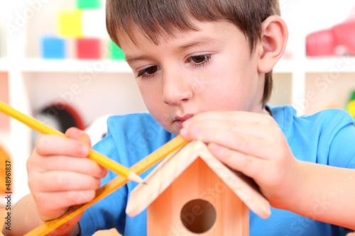 Obraz na płótnie Cute little boy makes birdhouse for birds