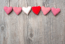 Red Hearts Hanging Over Wood Background