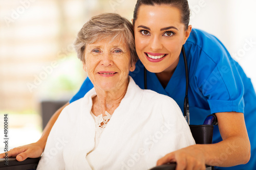 Láminas  happy senior woman on wheelchair with caregiver