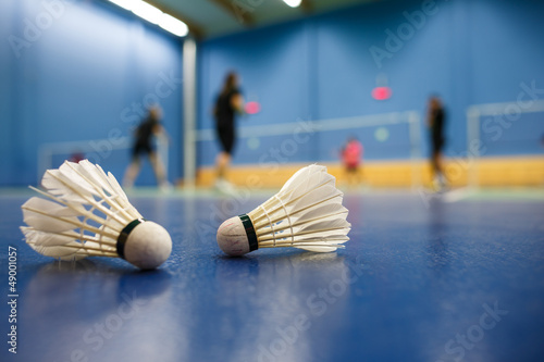 Photo badminton - badminton courts with players competing; shuttlecock