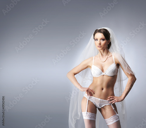 A young and sexy brunette bride posing in white lingerie