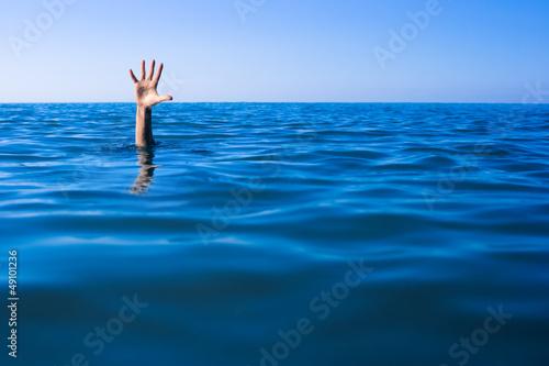 Fényképezés Help needed. Drowning man's hand in sea or ocean.