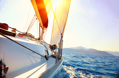 Yacht Sailing against sunset. Sailboat. Yachting. Sailing
