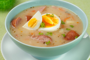 Fototapeta Do gastronomi White borscht with eggs and white sausage.Polish easter soup