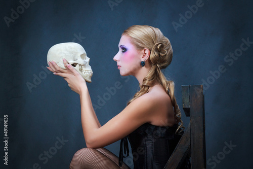 Photo  Woman with a skull, studio shot