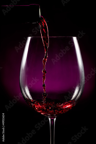 Foto Llenando la copa de vino sobre fondo negro