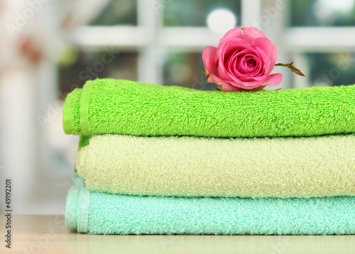 Valokuva  Stack of towels with fragrant flower on window background