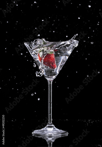 Poster Eclaboussures d eau Martini drink splashing out of glass on black background