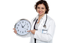 Pretty Doctor Pointing Out Time On Wall Clock