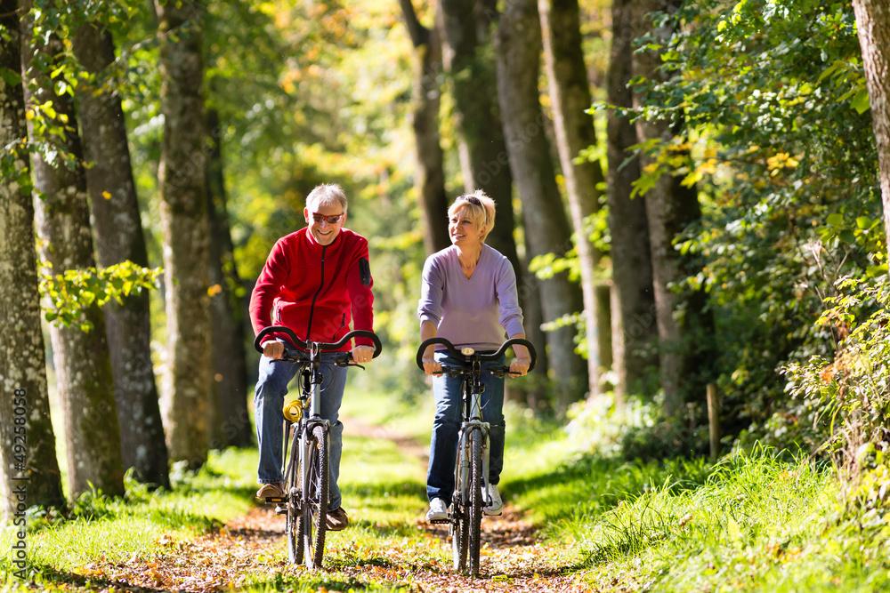 Fototapeta Seniors exercising with bicycle
