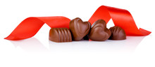 Four Chocolate Candies In Heart Shape And Red Ribbon Isolated On