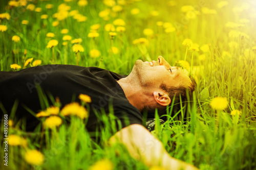 Tuinposter Ontspanning man lying on grass at sunny day
