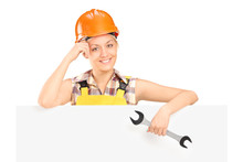 A Smiling Female Worker Holding A Wrench And Standing Behind Pan