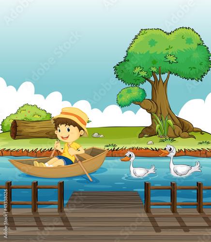 Aluminium Prints River, lake A boy riding on a boat followed by ducks